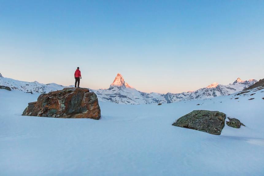 un om pe un varf de munte cu zăpadă - foto de Joshua Earle - unsplash.com