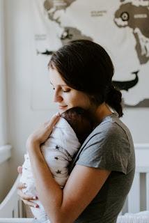 o femeie cu un bebeluș în brațe - foto de Kelly Sikkema - unsplash.com
