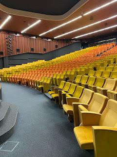 o sală de teatru sau de biserică cu scaune colorate - foto de  Maria Nazipova - unsplash.com